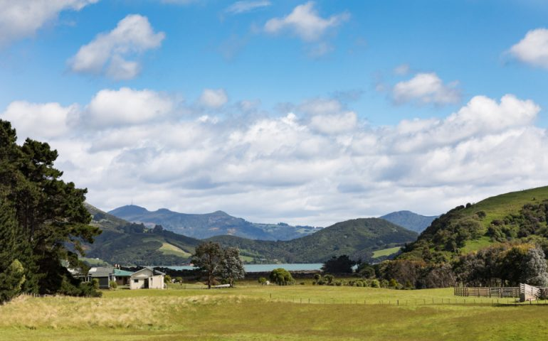 Farm house and paddock in rural Otago Peninsula with coastline and mountains in distance. A typical New Zealand rural scene.